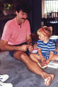 Caitlin and her dad open a present (a Barbie) on her birthday.