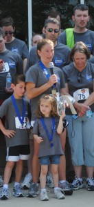 Angie Hipsher speaking at the GYRIG 5K run/walk in Indianapolis in June 2012. Her husband sands behind her and their two children.