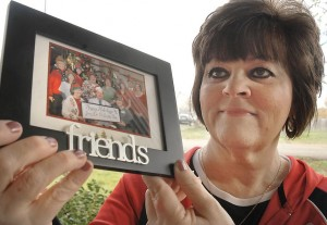 Paula Bussey holds a picture of her friends who supported her during her recent cancer treatment. Kevin Harvison